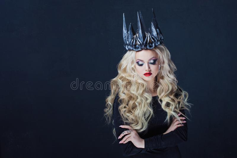Portrait of a Gothic Queen. Beautiful young blonde woman in metal crown and black cloak. Mystical image stock image