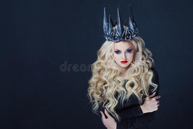 Portrait of a Gothic Queen. Beautiful young blonde woman in metal crown and black cloak. royalty free stock photography
