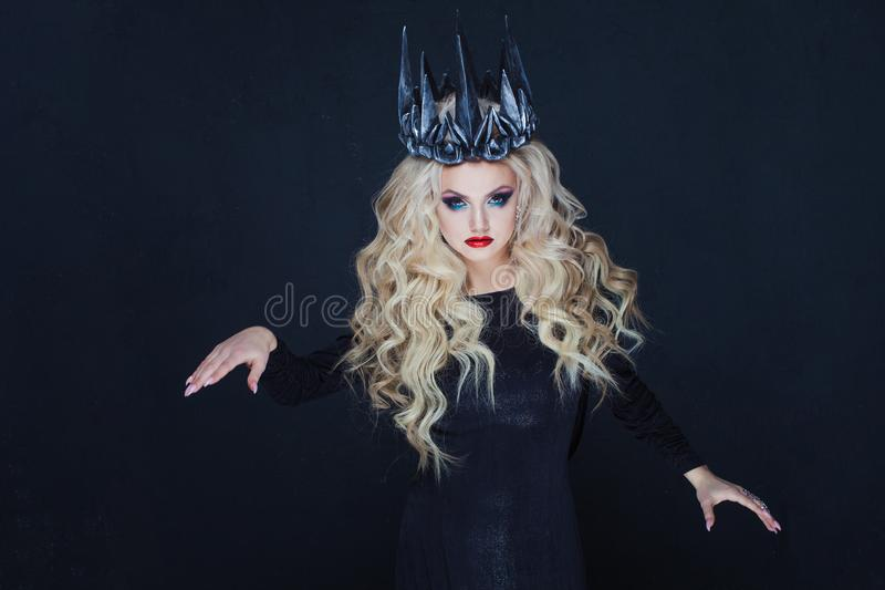 Portrait of a Gothic Queen. Beautiful young blonde woman in metal crown and black cloak. Mystical image stock photo