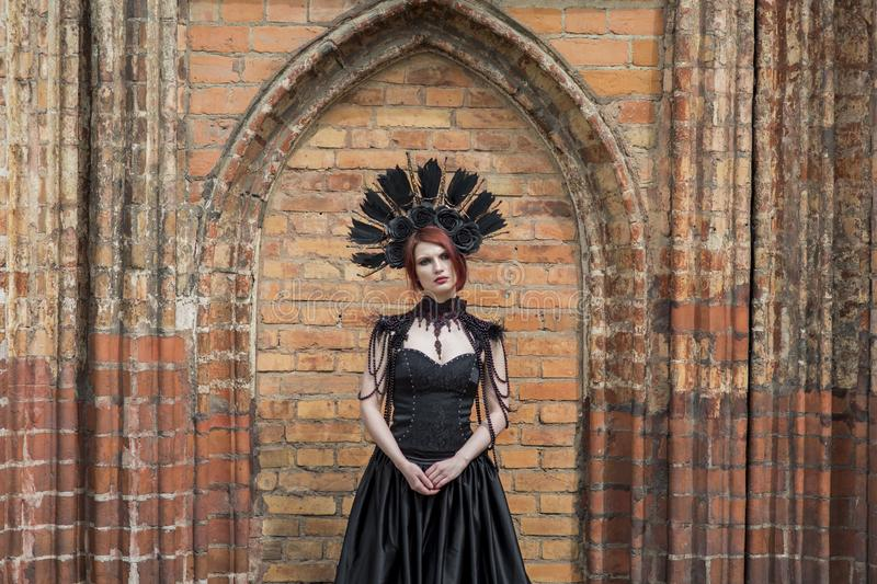 Portrait of Gothic Woman in Black Dress. Wearing Artistic Feather Crown. Posing Against Old Castle Gates. Portrait of Gothic Woman in Black Long Dress. Wearing royalty free stock image