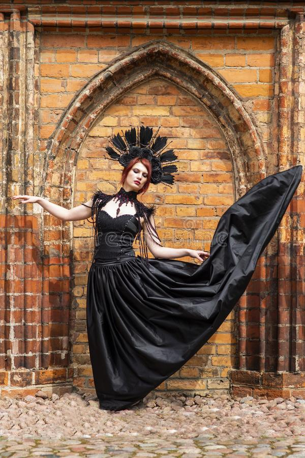 Portrait of Gothic Woman in Black Flying Dress. Wearing Artistic Feather Crown. Posing Against Old Castle Gates. Vertical Image Composition royalty free stock photo