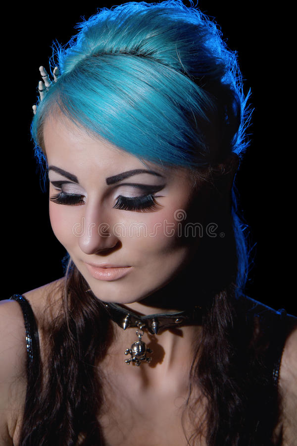 Portrait of Gothic woman with blue hairs. Closeup portrait of gothic woman with blue hairs isolated on black royalty free stock images