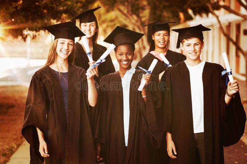 Portrait of graduate school kids standing with degree scroll in campus royalty free stock photography