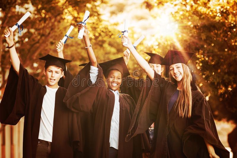 Portrait of graduate school kids standing with degree scroll in campus stock photography