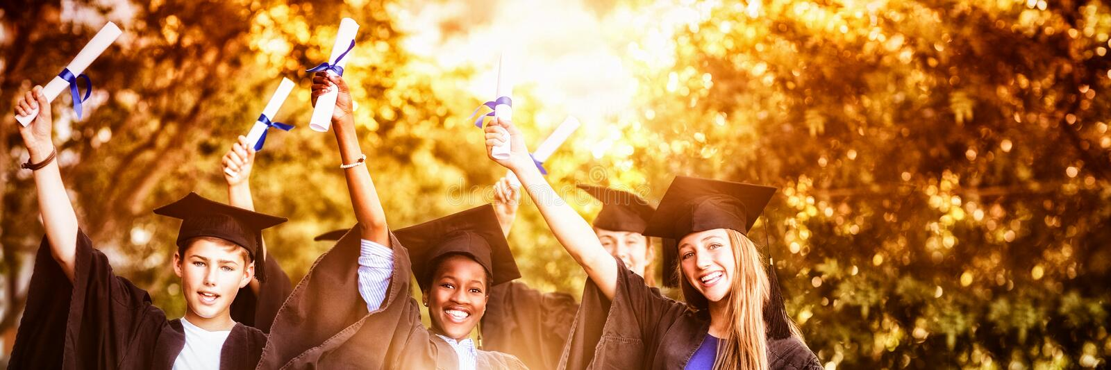 Portrait of graduate school kids standing with degree scroll in campus royalty free stock images
