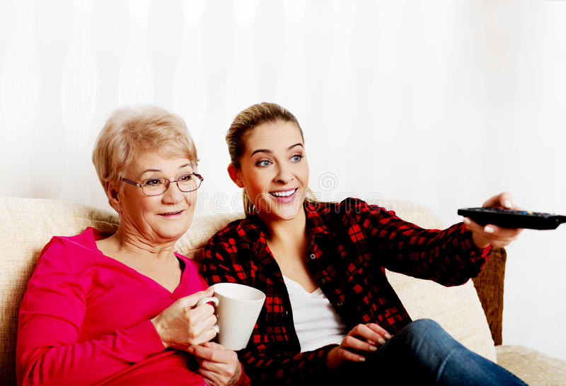 Portrait of granddaughter and grandmother sitting on couch and watching TV royalty free stock photography