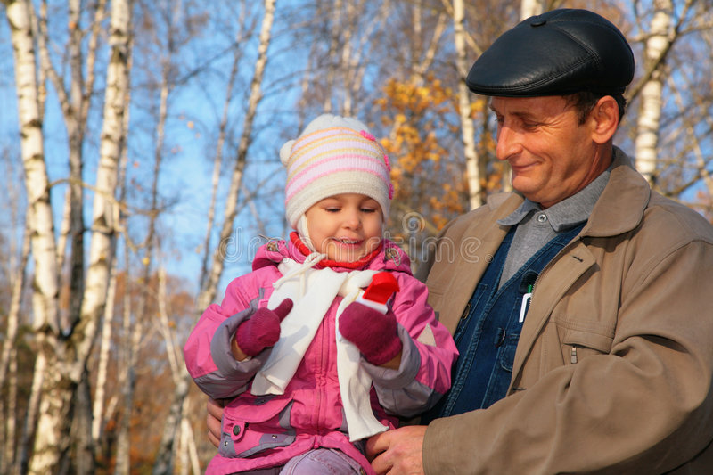 Portrait of grandfather with granddaughter in wood stock image