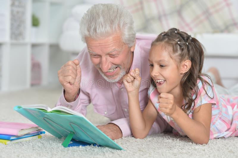 Portrait of grandfather reading book with his little granddaughter. Grandfather reading book with his little granddaughter at home royalty free stock image
