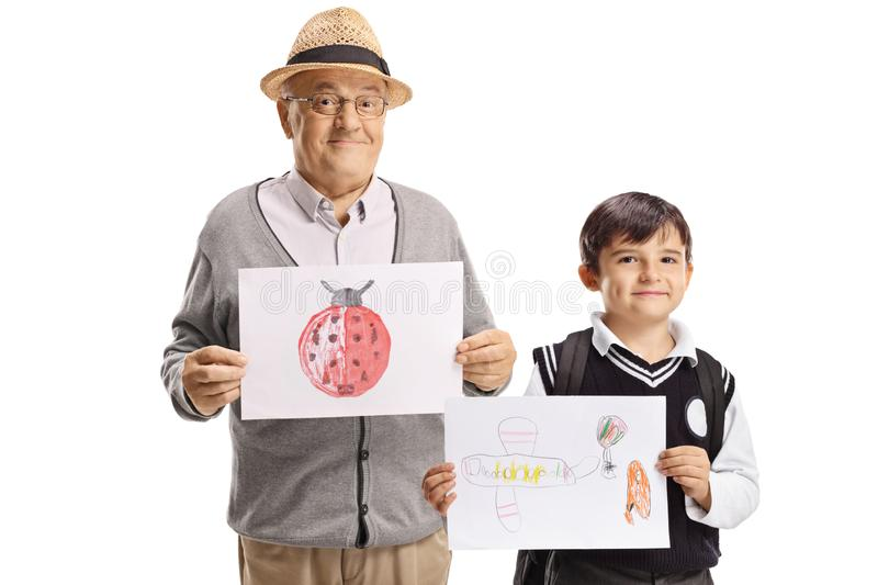 Portrait of a grandfather and schoolboy holding drawings and smiling royalty free stock photo