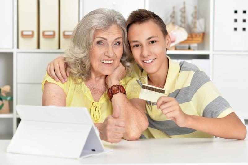 Portrait of grandmother and boy using modern laptop shopping online royalty free stock photo