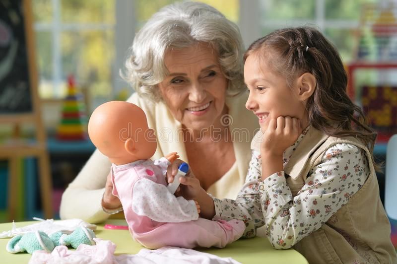Grandmother and child play. Portrait of grandmother and child play with baby doll royalty free stock image