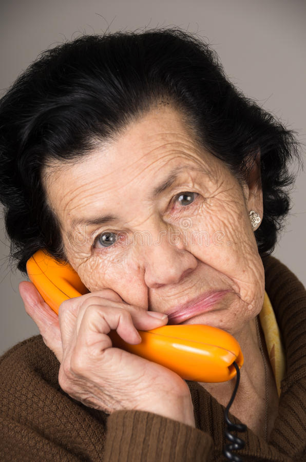 Portrait of grandmother old woman talking on the. Closeup portrait of sad grandmother old woman talking on the phone stock photography