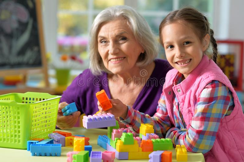Portrait of grandmother playing with her little granddaughter at home. Grandmother playing with her little granddaughter at home stock images