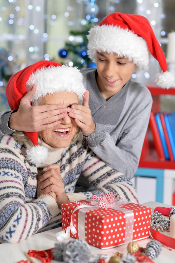 Portrait of a grandmother and teen boy. Portrait of smiling Grandmother and teen grandson celebrating Christmas royalty free stock images