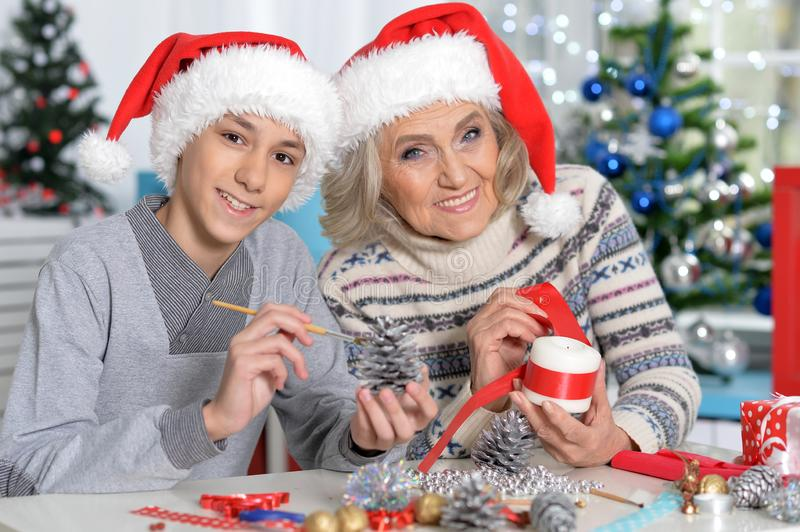Portrait of a grandmother and teen boy. Portrait of smiling Grandmother and teen grandson preparing for Christmas stock image