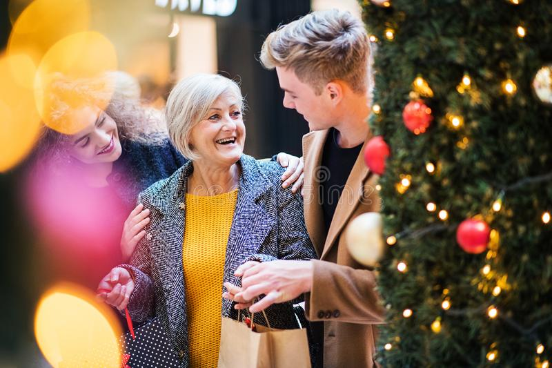 A portrait of grandmother and teenage grandchildren in shopping center at Christmas. royalty free stock images