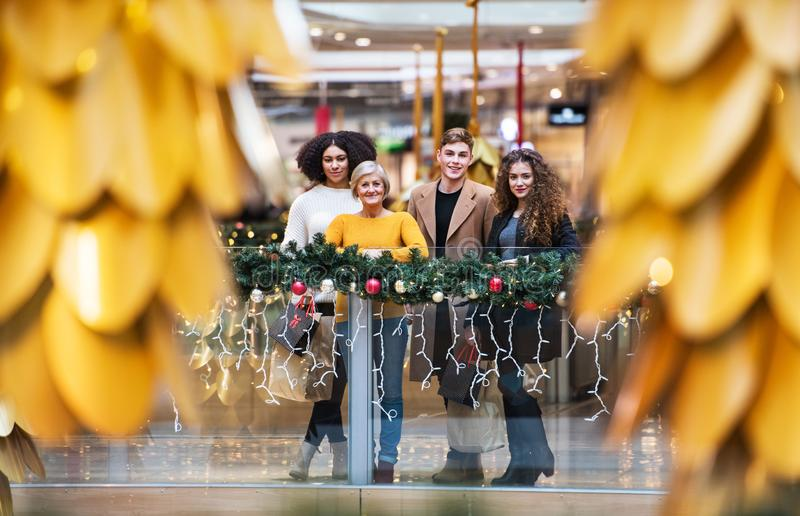 A portrait of grandmother and teenage grandchildren in shopping center at Christmas. royalty free stock photography