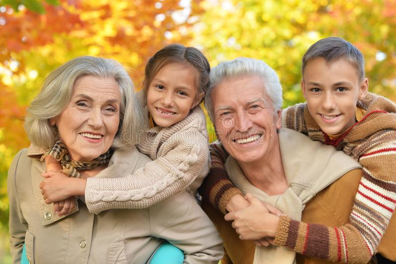 Grandparents with grandchildren posing outdoors in autumn stock photo