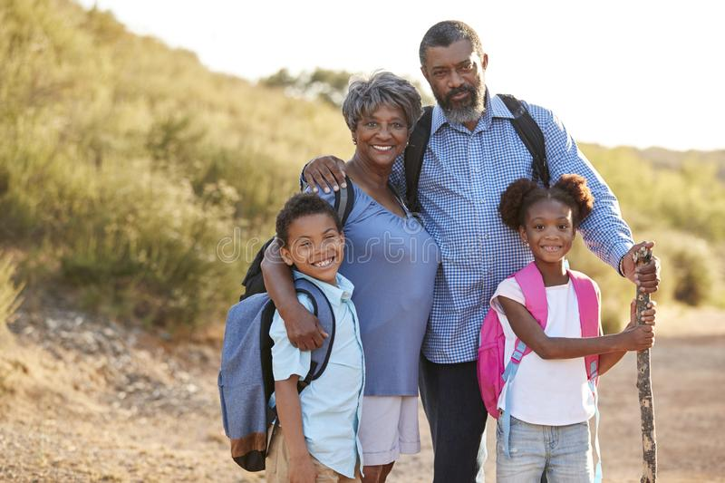 Portrait Of Grandparents With Grandchildren Wearing Backpacks Hiking In Countryside Together royalty free stock images