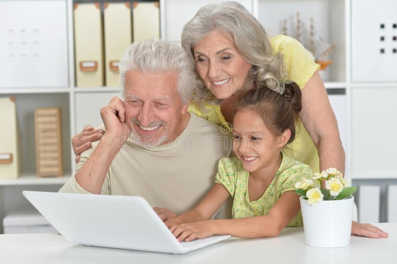 Grandparents with her granddaughter using laptop at home stock photos