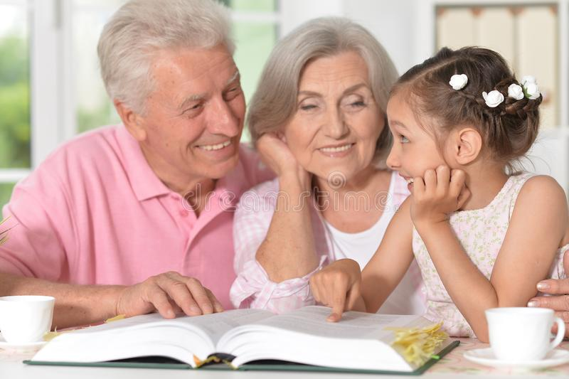 Portrait of grandparents reading book with little granddaughter. Grandparents reading book with little granddaughter at home stock photos
