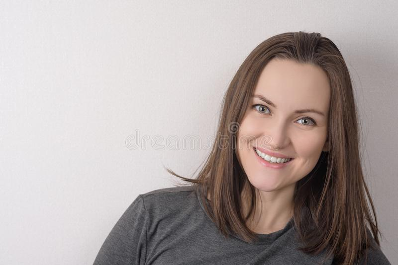 Portrait of green-eyed brown-haired woman on light background royalty free stock photo