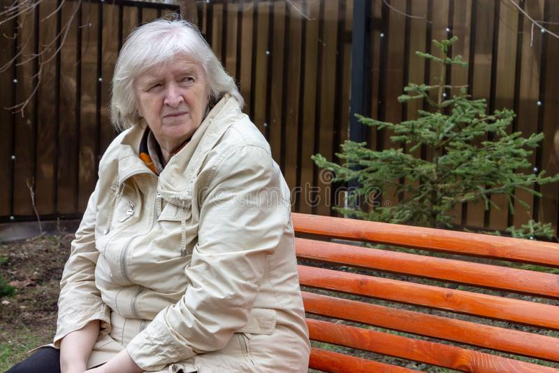 Portrait of the grey haired sad elderly woman sitting on the the park bench stock image