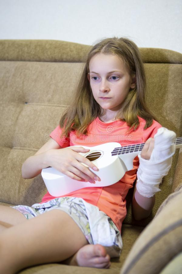 Portrait of Grieving Caucasian Girl  With Injured Hand In Plaster Playing Hawaiian Guitar Indoors royalty free stock photography