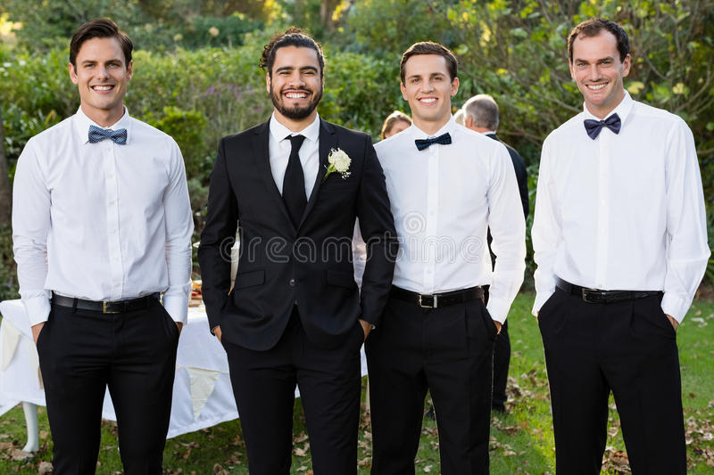 Portrait of groom and groomsmen standing with hands in pocket stock image