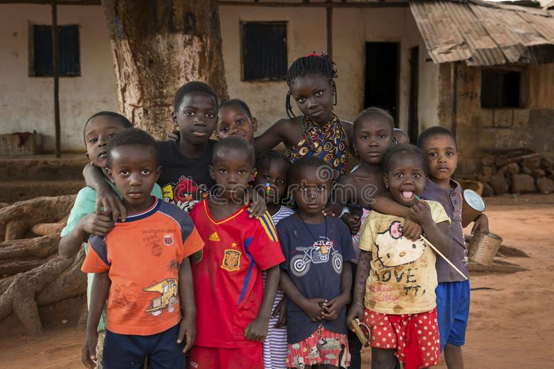 Portrait of a group of children in front of a house in the in the town of Nhacra. Nhacra, Republic of Guinea-Bissau - January 28, 2018: Portrait of a group of royalty free stock photo