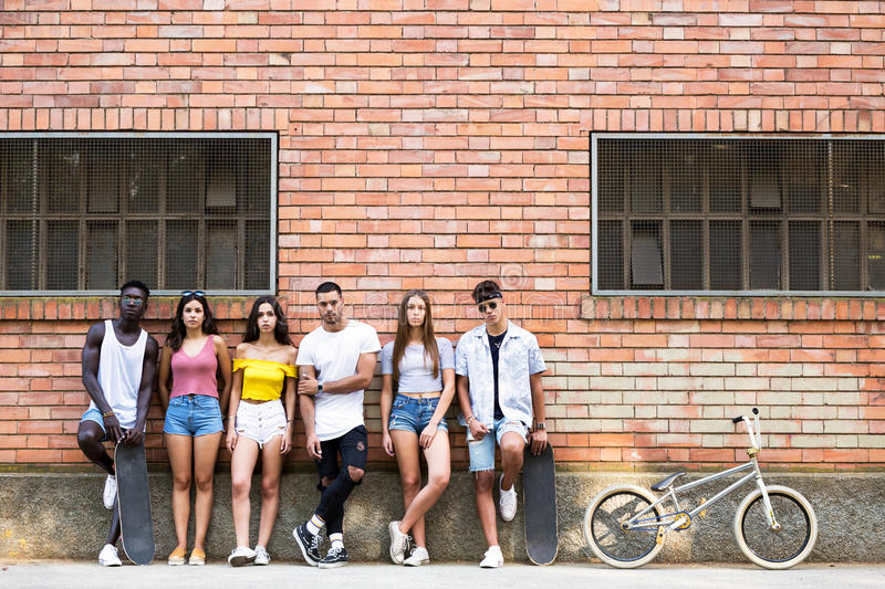 Group of young hipster friends looking at camera in an urban area. Portrait of group of young hipster friends looking at camera in an urban area stock photos