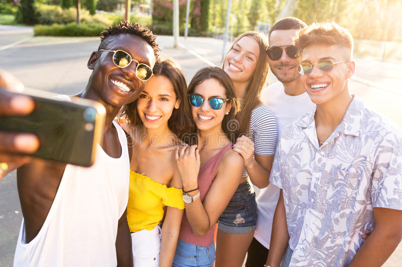 Group of young hipster friends using smart phone in an urban area. Portrait of group of young hipster friends using smart phone in an urban area stock photo