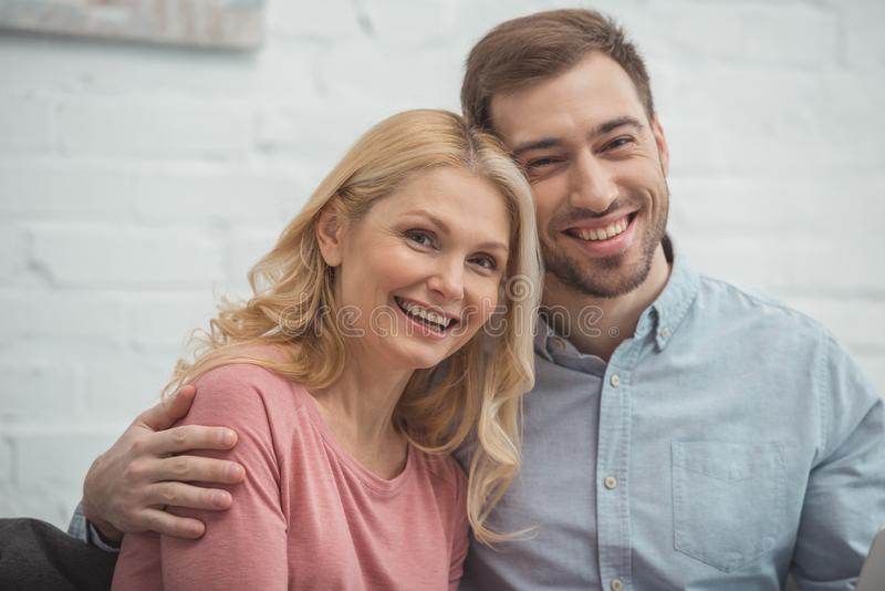 Portrait of grown son hugging smiling mother and looking. At camera royalty free stock photo