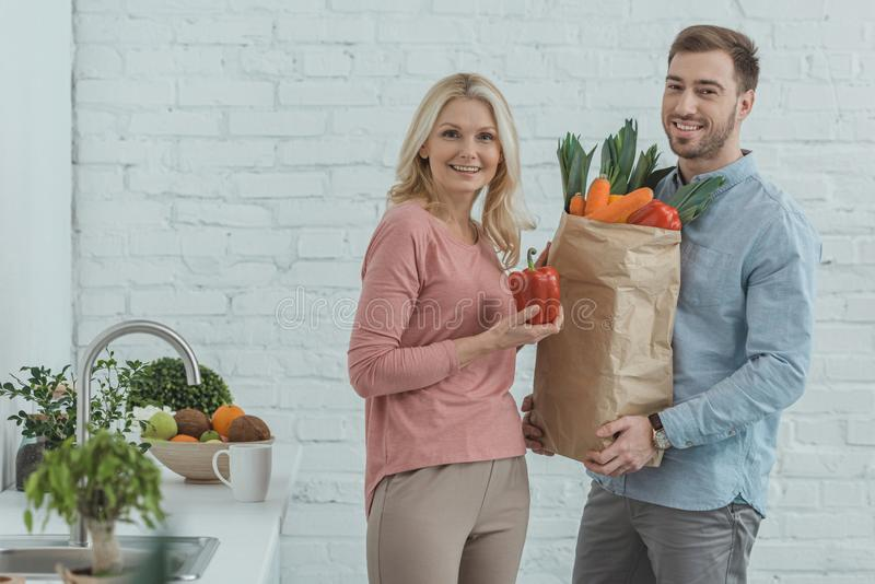 Portrait of grown son and mother with paper bag full of fresh vegetables for dinner. At home royalty free stock photo