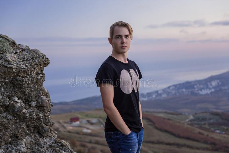 Portrait in growth. Young attractive man standing on the top of mountains stock image