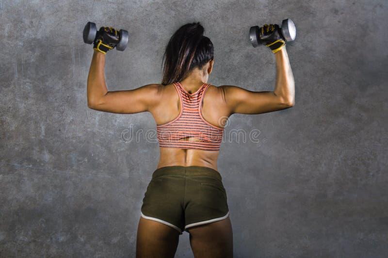 Portrait grunge de style de la publicité de sport de jeune femme sportive avec le corps arrière et convenable fort tenant des hal photographie stock libre de droits