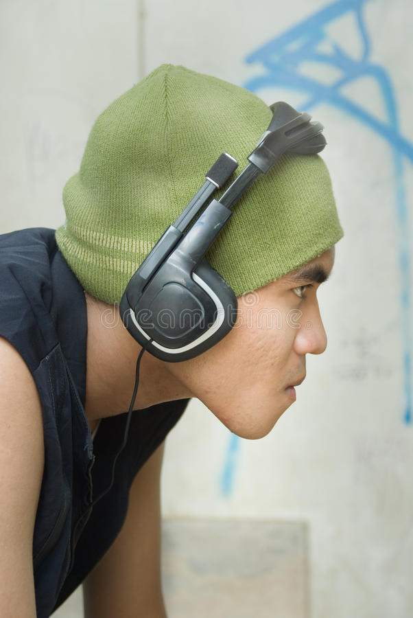 Portrait of grunge rapper. Closeup side view or profile portrait of tough young grunge Hispanic urban rapper dude with cap and headphone against a wall with stock images