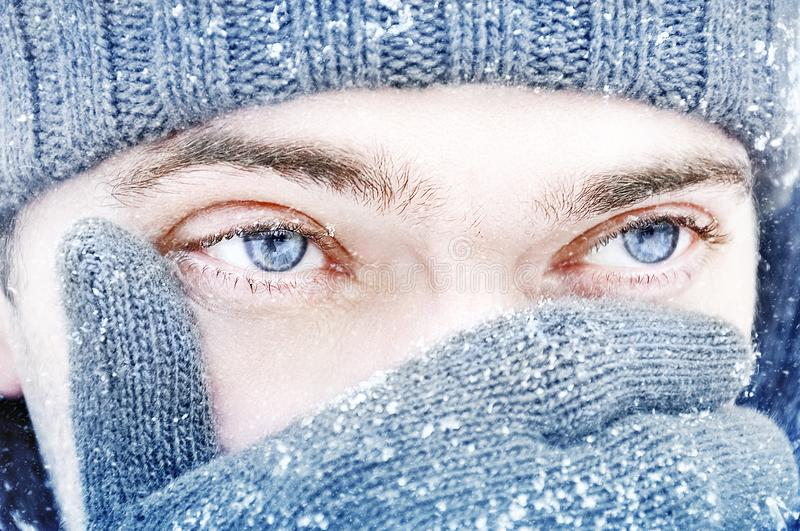 Portrait of a guy with blue eyes against a background of falling snow. Beautiful snowy weather. Snowing. Christmas image.  royalty free stock images