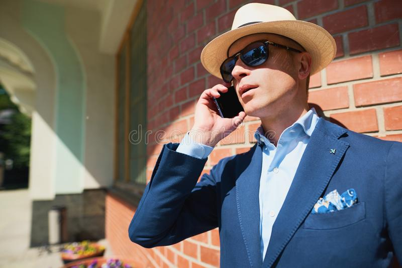 Portrait of a guy in a jacket on a brick wall background.Classic elegant formal men`s outfit. Businessman royalty free stock photography