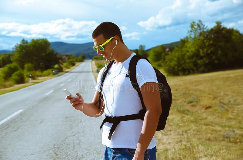 Guy on road trip, using smart phone to listen music with earphones. Portrait of guy on the road trip with the backpack, using smart phone to listen music with royalty free stock images