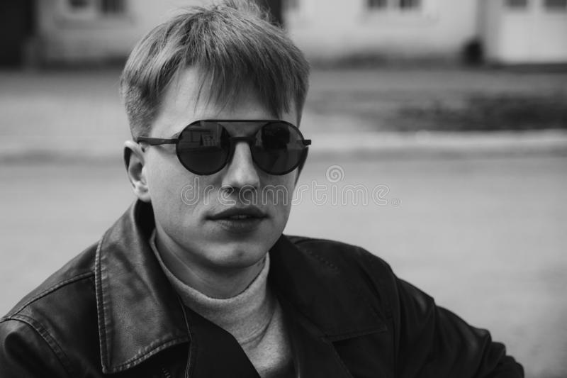 Portrait of a guy in round sunglasses and leather jacket stock image