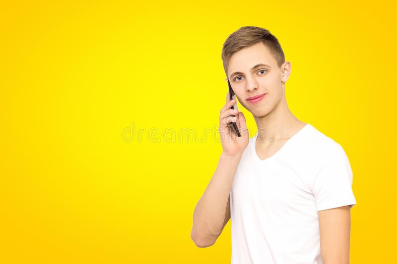 Portrait of a guy talking on the phone in the studio on a yellow background, isolate, a man on a yellow background stock photos
