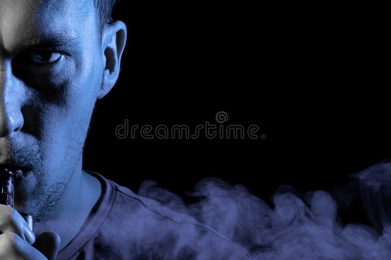 Portrait of a half face part of guy with a shadow on a serious face  with a backlight of blue color smoking a vape and exhaling stock photo