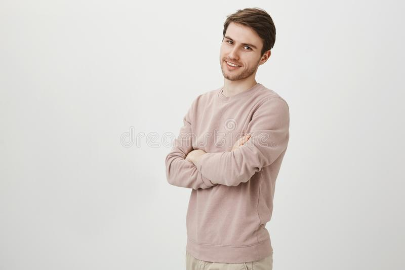 Portrait of half-turned attractive man with bristle standing with crossed hands with confident smile over gray. Background. Famous blogger gives speech about royalty free stock photography