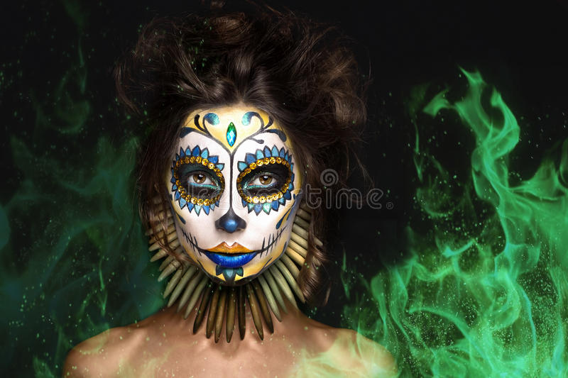 Portrait, halloween girl , dead mexican goddess Los Muertos in fire. Photo portrait of halloween girl in image of dead mexican goddess Los Muertos in green fire royalty free stock image