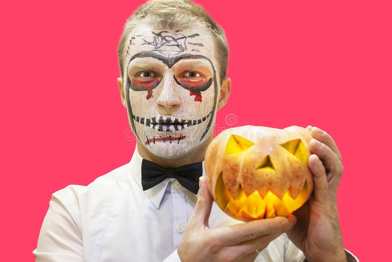 Portrait of halloween man with pumpkin. Man with halloween makeup. Halloween party concept. stock photo