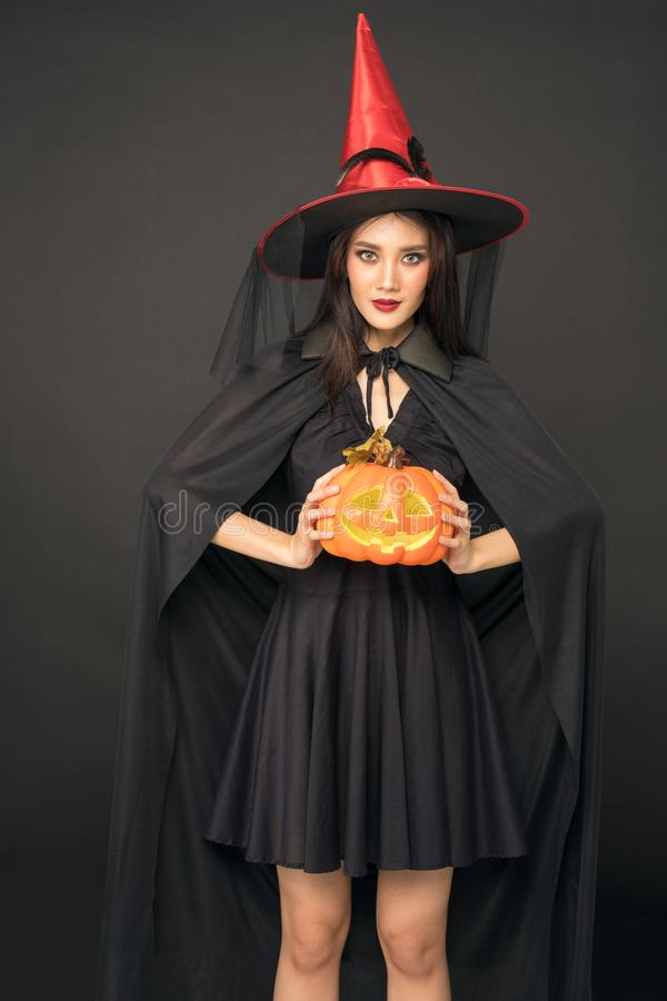 Portrait of Halloween Witch girl, Beautiful young Asian women  holding carved pumpkin royalty free stock photos