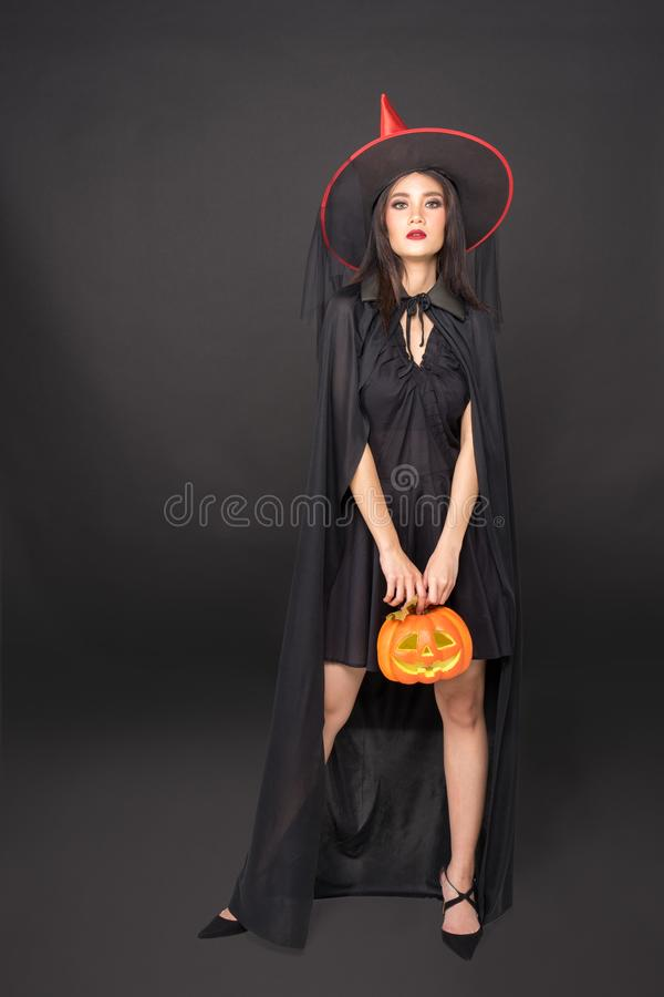 Portrait of Halloween Witch girl, Beautiful young Asian women holding carved pumpkin over black background stock photos
