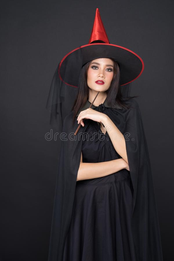 Portrait of Halloween Witch girl, Beautiful young Asian women holding magic wand stock photo