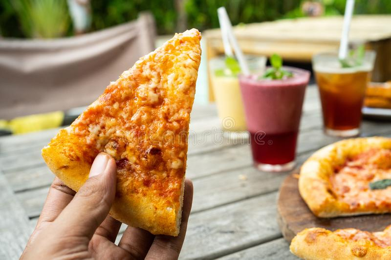 Portrait of hand with a slice of pizza look a yummy with yellow cheese. And the background is a table dish royalty free stock photography